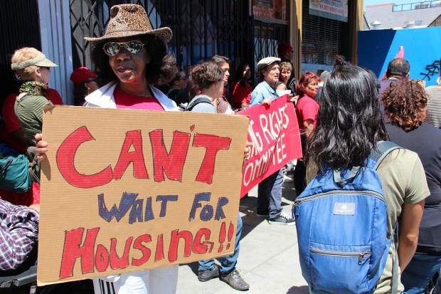 A woman marching for housing rights stops on Mission Street to listen to speakers talk about the luxury condos being constructed where the Giant Value store once stood. Photo by Molly Oleson