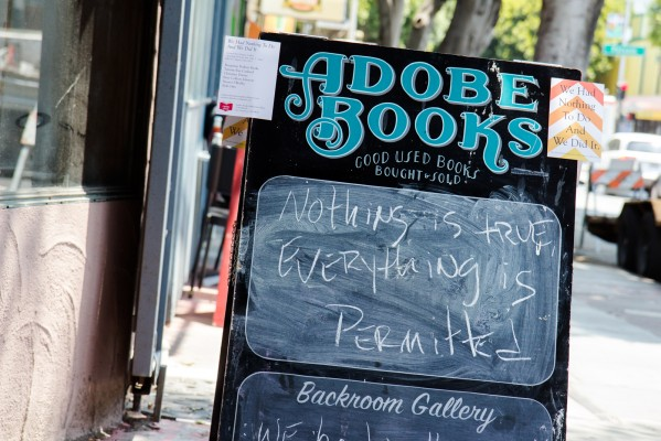 The Adobe Books sign is displayed on the sidewalk in front of the store's new location on 24th Street.