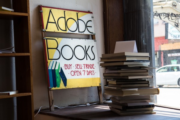An Adobe Books sign is propped up behind a stack of books next to the window.