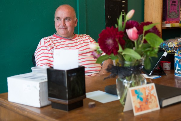 Andrew McKinley, founder of Adobe Books, sits at the counter at the store's new location.