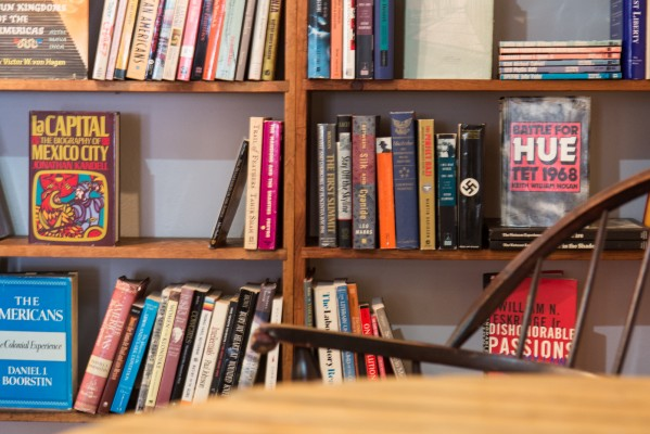 A table and chair by one of the bookshelves invite customers to sit down and read.