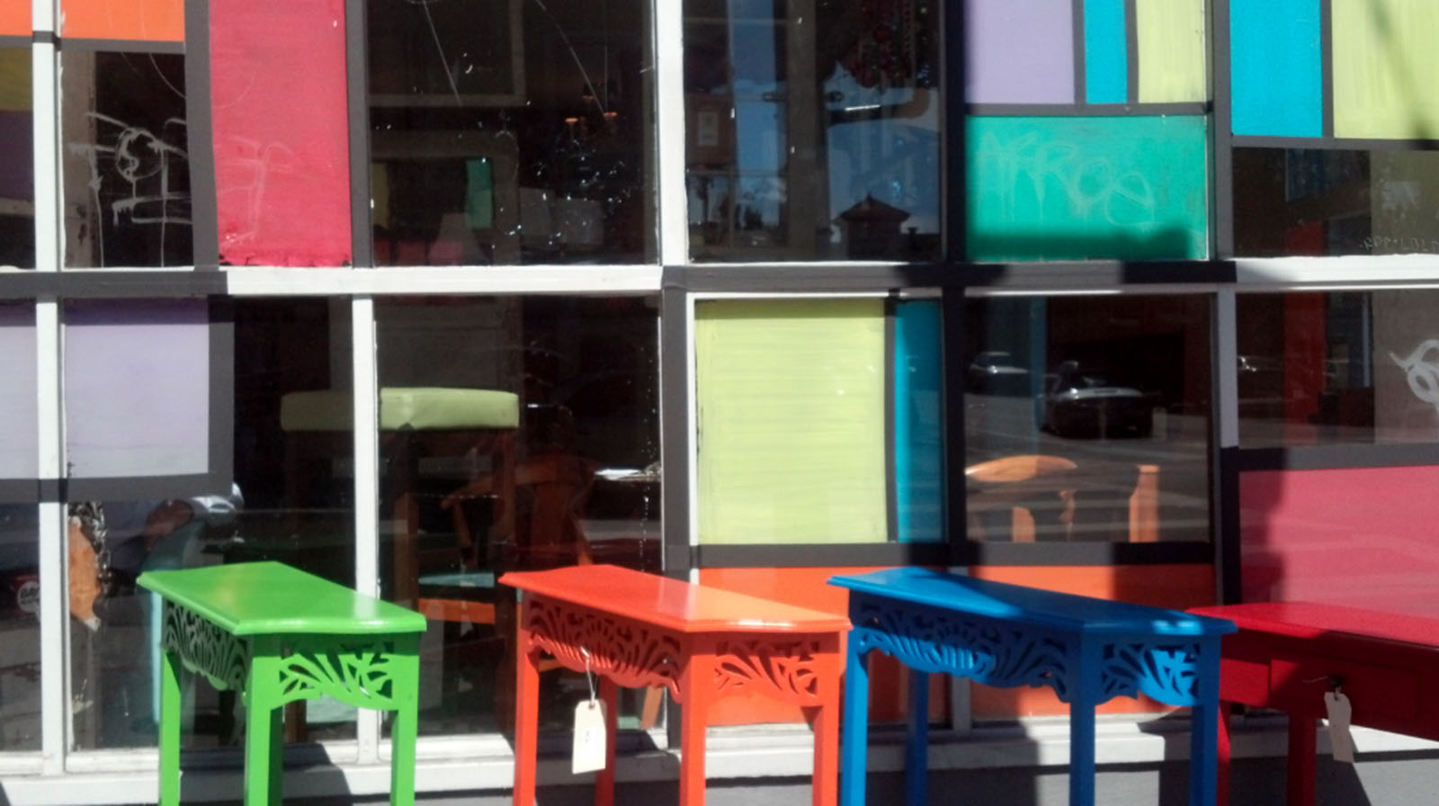Colorful tables are lined up outside of a shop on Valencia Street.