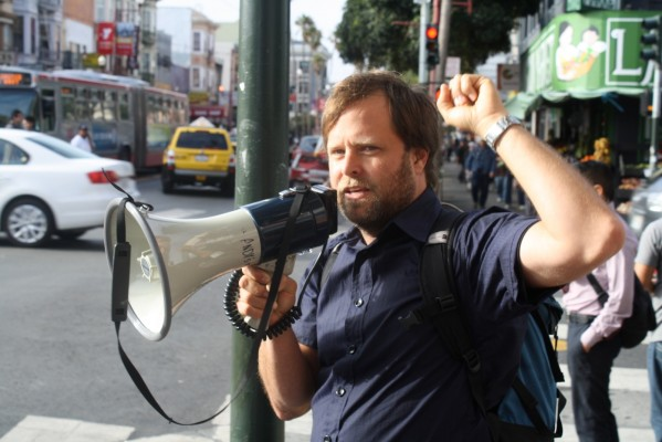Andy Blue speaks into megaphone at an protest of evictions at Redlick Building August 27, 2013. Photo by Daniel Hirsch.