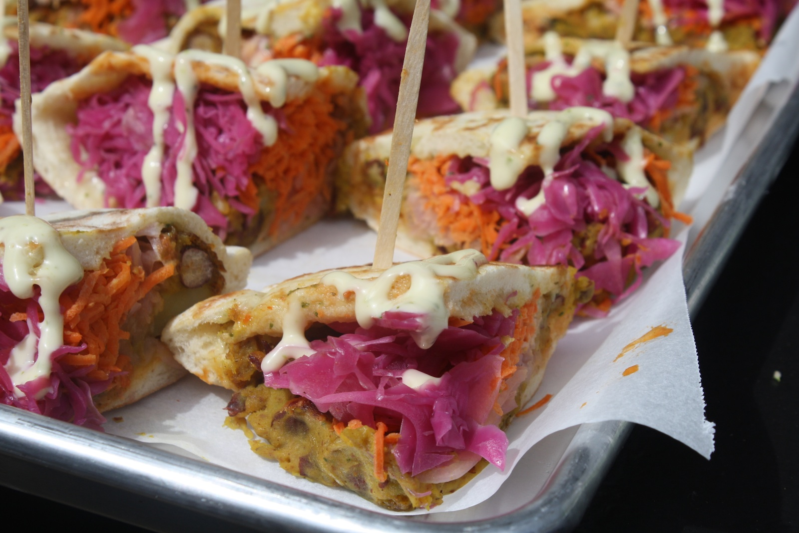 This colorful number, from Kama Food Labs, is an Indian street food sandwich of vegetable fritter in pita bread accessorized by charming pink pickled vegetables and paneer for pinache. Photo by Dan Hirsch.