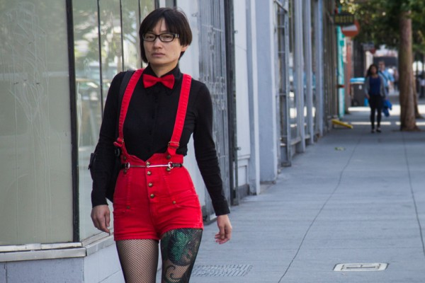 A woman in red and black walks up Valencia St.