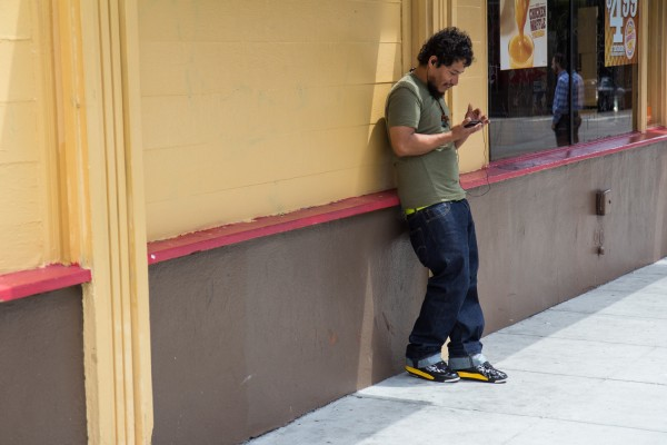 A man checks his cell phone on 22 St.