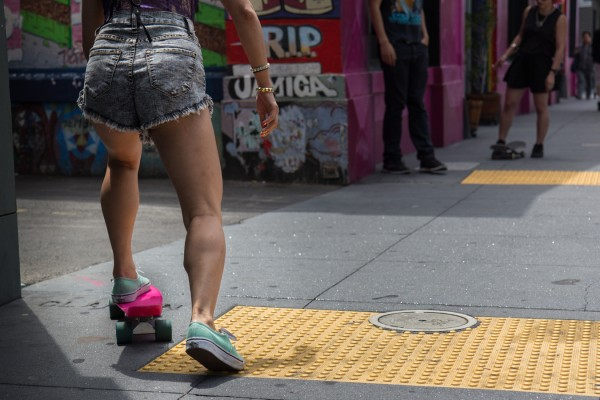 A girl gets ready to skateboard down Clarion Alley for a video. Photo by Marta Franco.