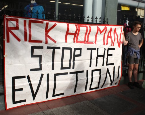Demonstrators hold sign protesting evictions from Redlick Building by owner Rick Holman. Photo by Daniel Hirsch.