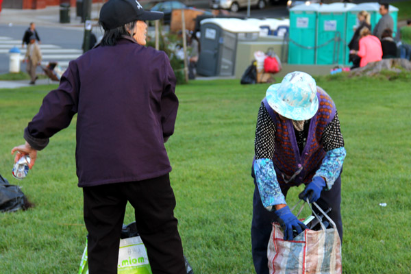 """Two women pick up aluminum cans and plastic bottles. Many people leave behind their trash with the expectation that it will be picked up by the recyclers. """"It's almost a symbiotic relationship,"""" said 29-year-old San Francisco resident Anthony Smith-Winters."""
