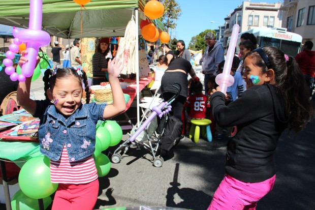 "Salem Perea (left) and Galilea Serrano play with their balloons. ""I love the face painting, the balloons and the food,"" said Serrano, age 7."