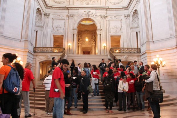 Immigrant rights activists stand in the foyer of City Hall after the Board of Supervisor's unanimous vote to limit immigration holds in San Francisco. Photo by Alexandra Garretón.