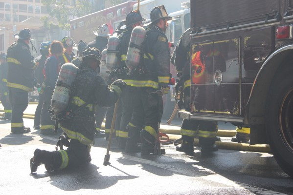 This firefighter rested on one knee after emerging from the burning building at 1450 Valencia. Photo by Greta Mart.