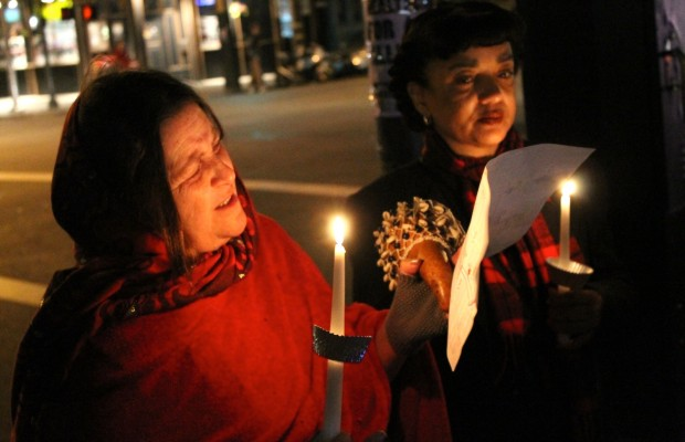 Patty Davis (left) surveys the route of the Las Posadas procession along 24th Street.