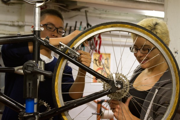 Bike mechanic Esther Cervantes helps Mission High student Yuxin Mao repair a bike. Photo by Courtney Quirin.