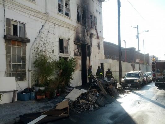 Firefighters clear debris from the Stevenson Street fire. Photo by Daniel Hirsch.