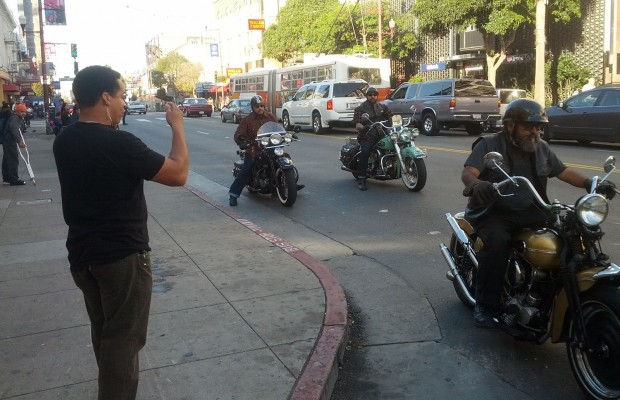 A production assistant waves on a trio of bikers for a Modelo commercial being filmed on Mission Street.