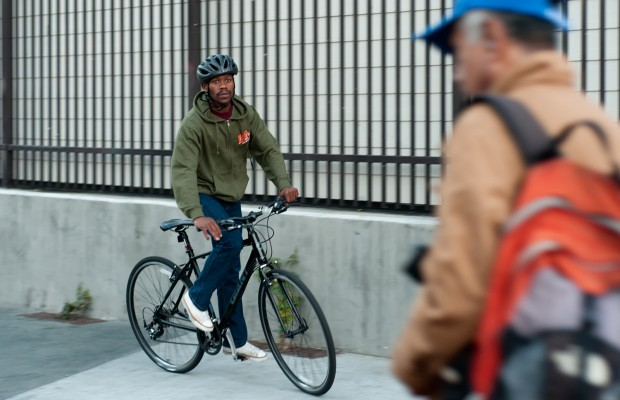 Dancer Brian Mtembu arrives at the performance in the role of a hipster on a bike.
