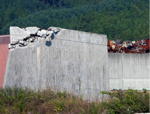 Part of the wall that was intended to hold back the wave. Behind is a pile of metal scrap which collected after the wave withdrew.
