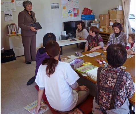 """Mission resident Tomoko Lipp meeting with local displaced people. She was teaching the group how to make roses out of old newspapers. The meeting took place in the small """"social"""" area which served the families living there."""