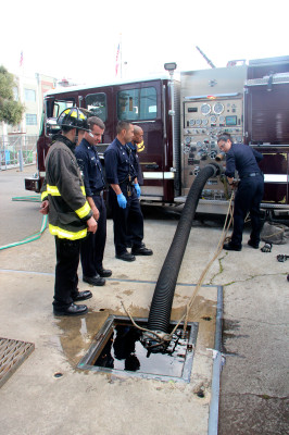 Carvajal (right) in the middle of a drafting exercise – learning how to get water from an alternative source into the fire engine in cases hydrants don't work. (Photo by Viktorija Rinkevičiūtė)