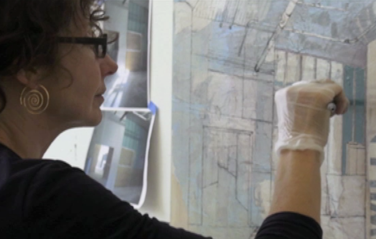 Catherine Mackey adds some detail to a canvas featuring one of her portraits of the urban environment