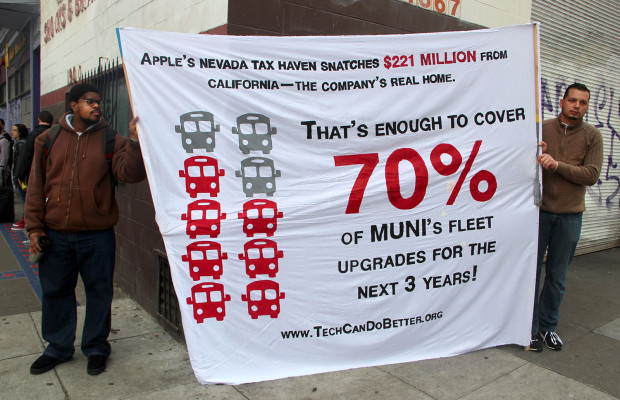 SEIU members hold sign demanding Apple pay more of its taxes in California.
