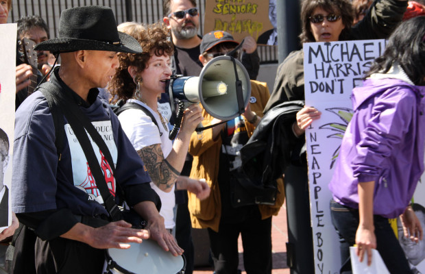 Benito Santiago (left) drums while Erin McElroy speaks into the megaphone at the anti-eviction protest.