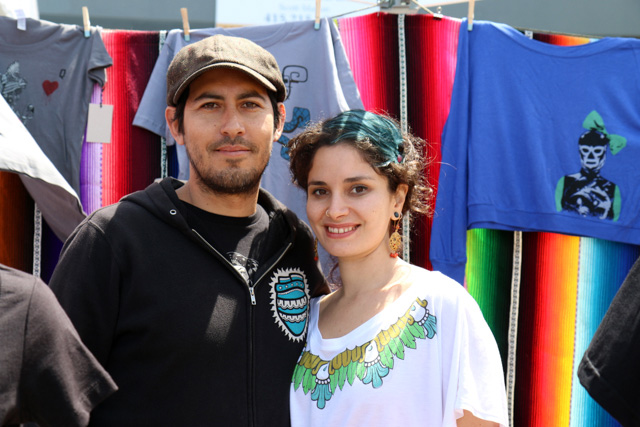 """Esmerelda Padilla and Javier Martinez of Zia SF, who make original hand printed apparel. Esmerelda, who grew up in the Mission and first started printing at Mision Grafica, says """"I like Carnaval because it brings everyone out of the woodwork. There's nothing pretentious or hipster about it. It's a little microcosm. It still has the same flavor even though the city is changing.""""  Photo by Claire Weissbluth"""