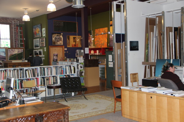 The back of the gallery hosts a shelves filled with art-related books, as well as several dozen more pieces of art. Photo by Joe Rivano Barros.