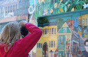 A tourist snaps photos of Balmy Alley's famous murals. Airbnb visitors spent $8.3 million in the Mission District between April 2013 and March 2014. Photo by Leslie Nguyen-Okwu.