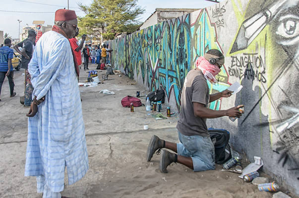 Wall #1: On a busy thoroughfare, the theme of the day is education. Pioneer Dakar graffiti artist Big Key paints, while an interested neighborhood gentleman observes.