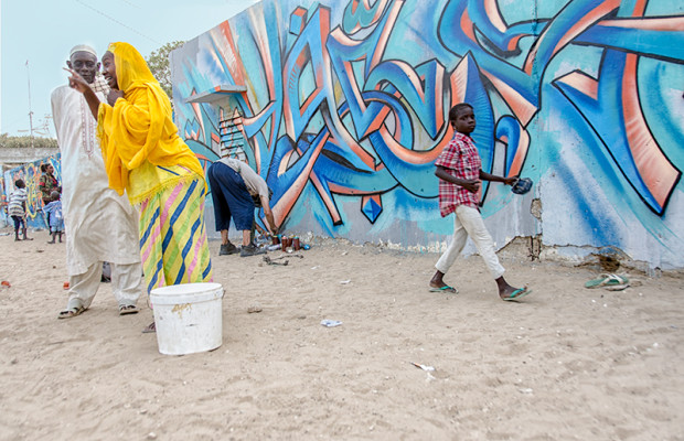 Wall #2: Neighbors young and old come out to show their enthusiasm as artists paint all the houses on their sandy lane.