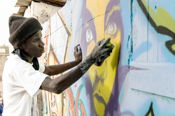 Wall #2: While the people party, this young graffeur concentrates on his mural.