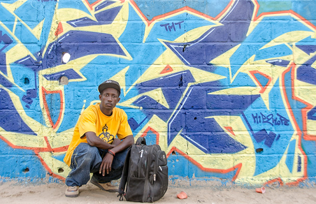 Wall #2: Mow in front of his mural. At the end of a long day, he has packed his equipment and is ready to go.