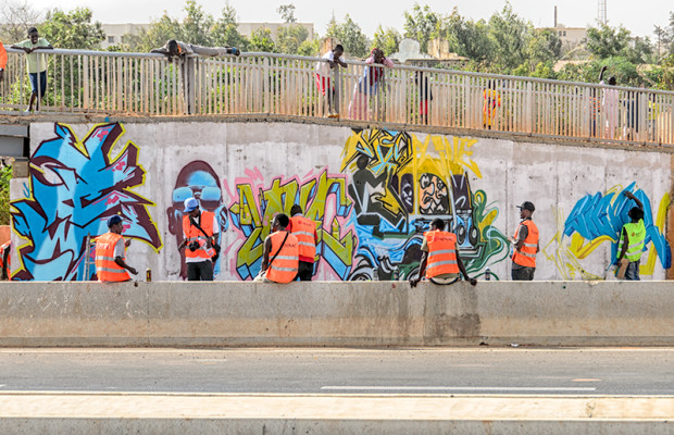 Wall #3: The Senegal Toll Highway. While the artists paint the wall of an overpass, neighborhood children get involved.