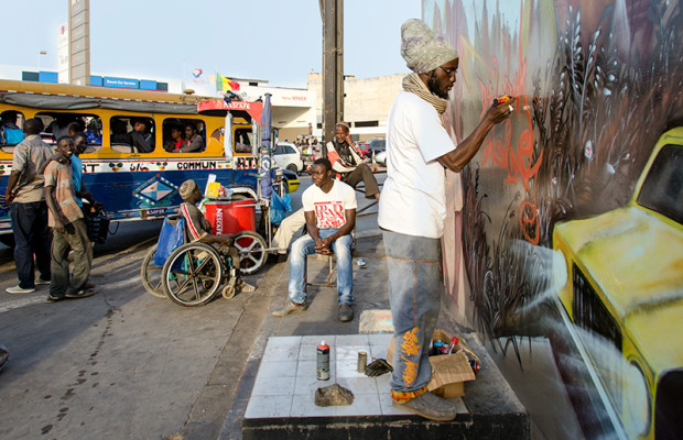 Leading Dakar graffeur Docta paints a wall against a background of Dakar icons: a Nescafe street vendor and a legendary Car rapide.