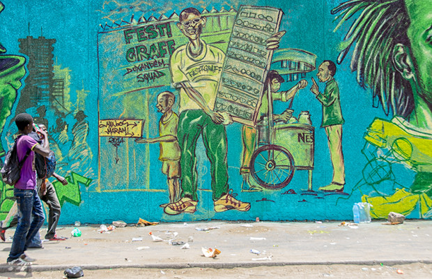 Wall #4: Along the marketplace of the Médina neighborhood, artists paint scenes from Dakar daily life. Manoos, from Burkina Faso, paints street vendors, one selling sun glasses, another selling Nescafe coffee like the vendor in Slide 13.