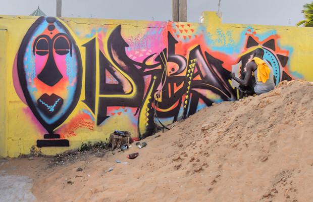 Graffeur Diablos paints the back wall of the Artists' Village.