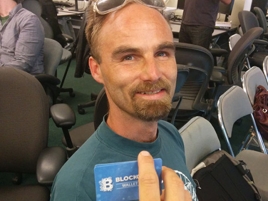"""Guests were tempted to attend the Bitcoin Beginners Fair with the prospect of free Bitcoin. Emil Reiman displays the two gift cards each participant received, amounting only to several """"millibits,"""" since each complete Bitcoin is worth several hundred dollars. Photo by Laura Wenus"""