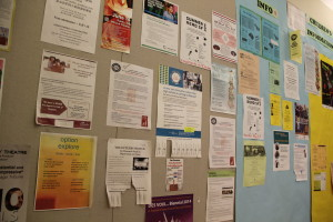 A central hallway houses dozens of flyers, promoting reading groups, language tutorials, and advertisements from local businesses and organizations. Photo by Joe Rivano Barros.