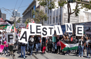 """People holding letters that make up the word """"Palestine"""" at Civic Center's United Nations Plaza. Photo by Marc Hors"""