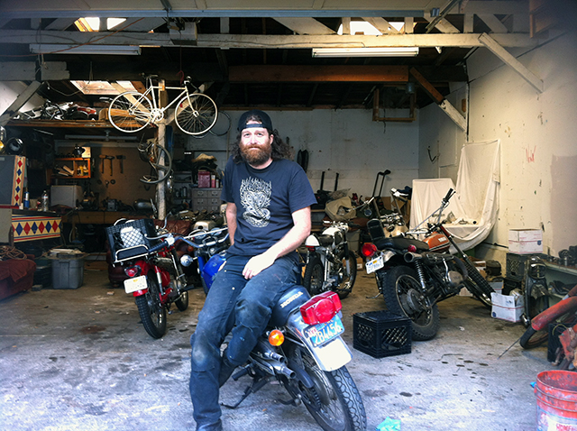 Dave West, 42, in the garage he rents to store and work on his motorbikes. The garage is scheduled for demolition to make room for a three-story single-family dwelling. Photo by Andrea Valencia