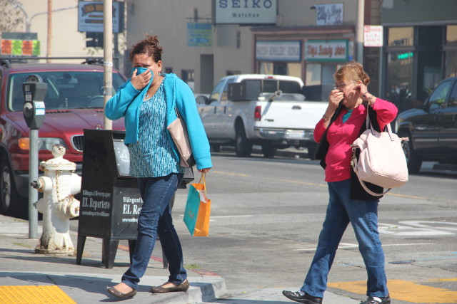 Two women shield their faces from the smoke on Capp Street near 22nd Street around 3:30 p.m. Photo by Leslie Nguyen-Okwu.