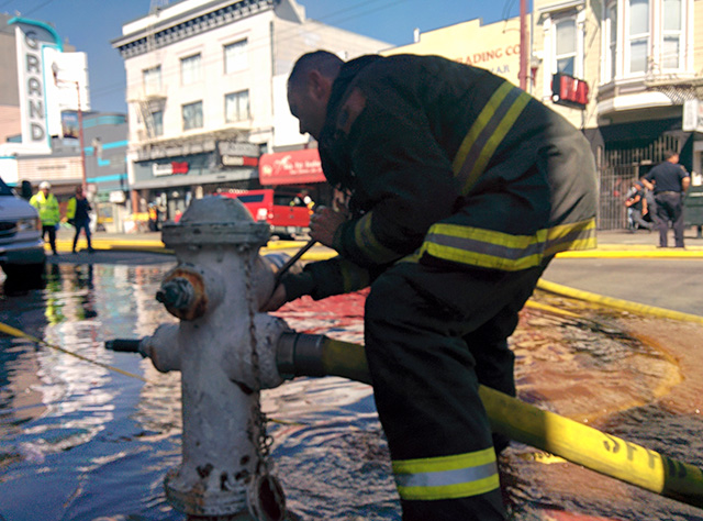 Firefighter connecting a hose to the hydrant on Mission Street and 23rd. Photo from around 3:48p.m. by Laura Wenus.