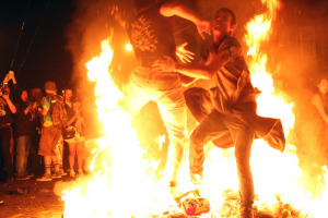 Fans clash while jumping at the fire. Photo by Rigoberto Hernandez.