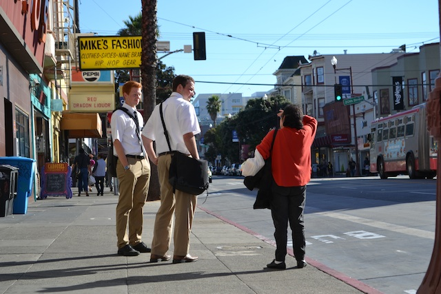 Elders Webster and Castleberry speak with woman at bus stop. Photo by Daniel Hirsch.