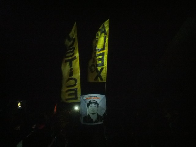 Banners raised behind image of Alex Nieto as march concluded on Bernal Hill. Photo by Daniel Hirsch.