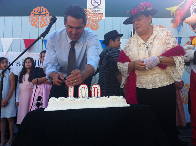 The school's principal Peter Avila lighting the cake's candle. Photo by Andrea Valencia