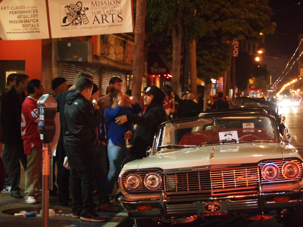 Low riders lingered outside the Mission Cultural Center late into the night, while police watched from across the street.