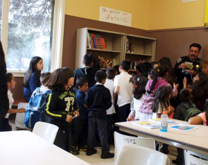 Kids crowd around the newly-installed bookcases at the Garfield Park clubhouse. Books borrowed from the library have no due dates.